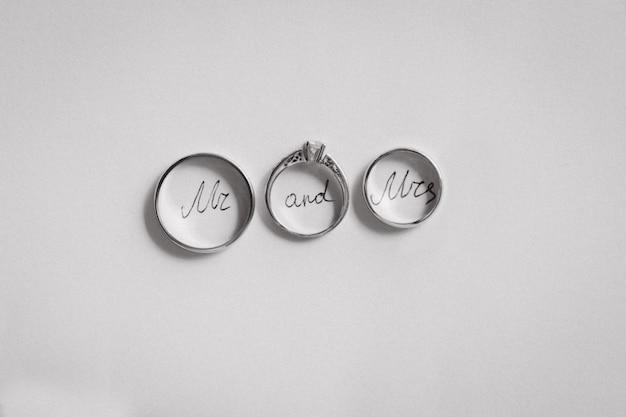 Dos cortezas nupciales y un compromiso sobre papel blanco. inscripción dentro de los anillos, sr. y sra.