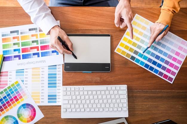 Dos creativos diseñadores gráficos que trabajan en la selección de colores y muestras, dibujando en una tableta gráfica.