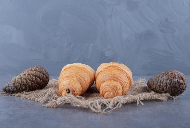 Dos croissants caseros frescos y cono de pino sobre fondo gris.