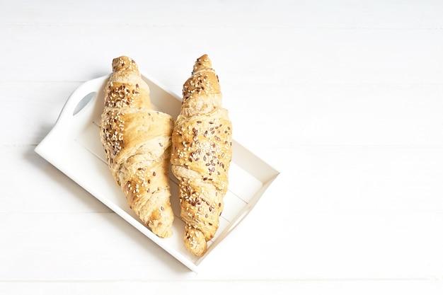 Dos croissants integrales en bandeja blanca. vista superior, espacio de copia