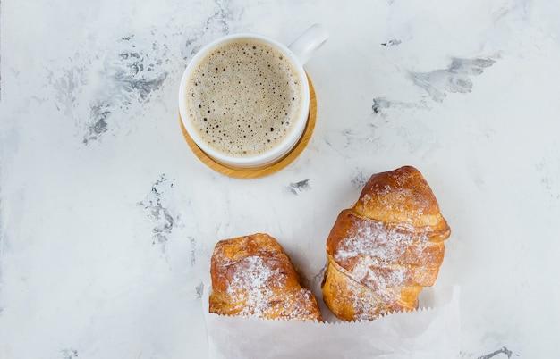 Dos croissants recién hechos en una bolsa de papel y una taza de café sobre un fondo de mármol, vista desde arriba, plano