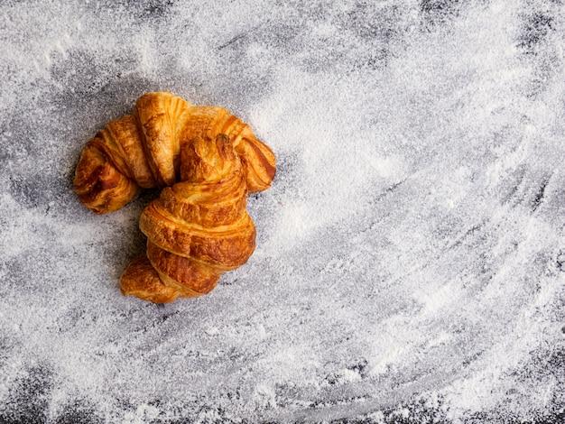 Dos cruasanes de mantequilla caseros frescos simples aislados sobre fondo de harina blanca. concepto de pastelería casera.
