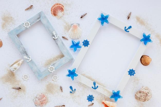 Dos cuadros en blanco con conchas marinas en mesa