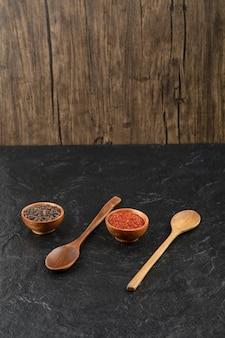 Dos cucharas de madera con cuencos de madera de bolas de pimienta y pimienta en polvo