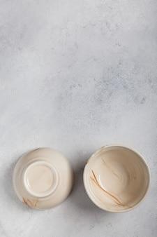 Dos cuencos de arcilla blanca sobre un fondo claro