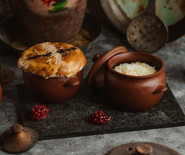 Dos cuencos de cerámica con pastel y arroz dentro.