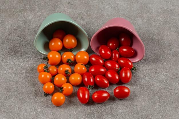 Dos cuencos de tomates volcados, sobre el mármol.