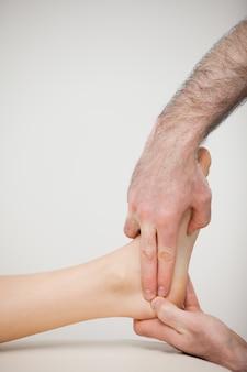 Dos dedos presionando el tendón de aquiles de un paciente
