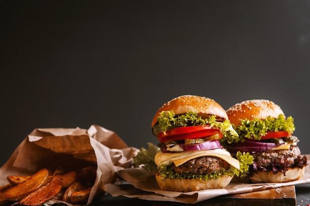 Dos deliciosas hamburguesas caseras deliciosas para picar carne de res. en la mesa de madera.