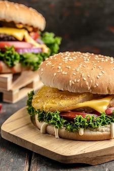 Dos deliciosas hamburguesas caseras de ternera, queso y verduras. alimentos grasos no saludables. imagen vertical. lugar para el texto.