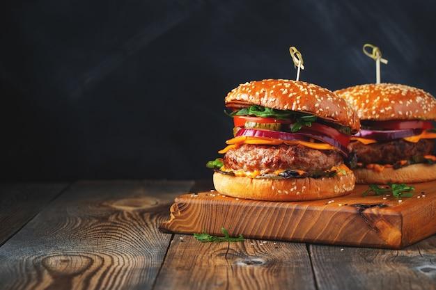 Dos deliciosas hamburguesas caseras de ternera, queso y verduras en una vieja mesa de madera. primer plano de alimentos grasos no saludables.
