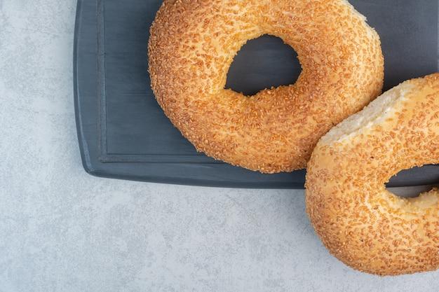 Dos deliciosos bagels frescos en un plato oscuro.