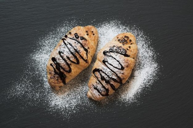 Dos deliciosos cruasanes recién horneados sobre fondo de pizarra. vista superior. desayuno.