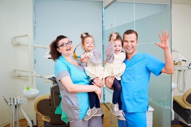 Dos dentista con niños en sus brazos sonriendo riendo el d
