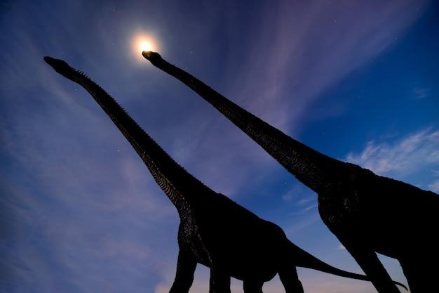 Dos dinosaurios de silueta en la noche oscura y el halo de la luna con fondo de estrellas y nubes