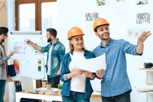 Dos diseñadores arquitectos posando con papeles