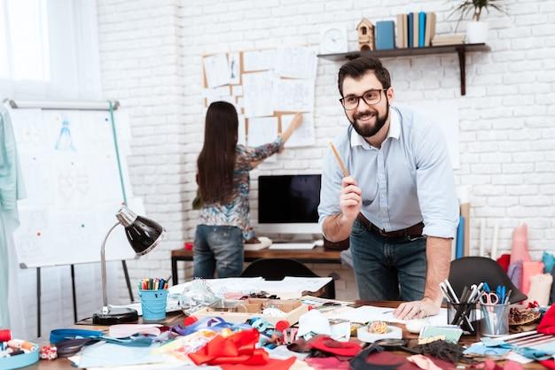 Dos diseñadores de moda dibujando con lápiz.