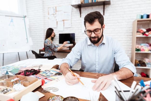 Dos diseñadores de moda dibujando sobre papel.