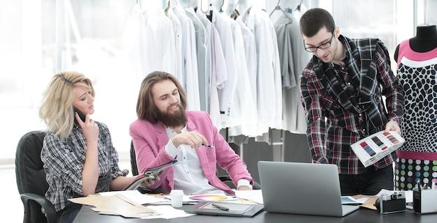 Dos diseñadores de moda están trabajando en la creación de ropa de mujer en el estudio.