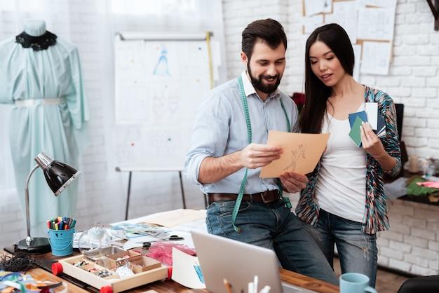 Dos diseñadores de moda miran dibujos y muestras