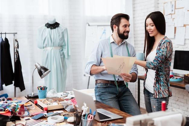 Dos diseñadores de moda mirando dibujo hablando.