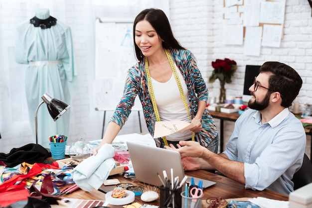 Dos diseñadores de moda que discuten el dibujo modelo.