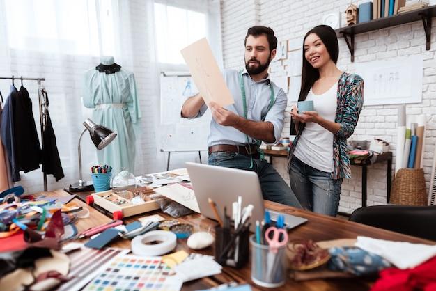 Dos diseñadores de moda que miran el dibujo que habla.