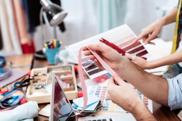 Dos diseñadores de moda que miran la paleta de colores.
