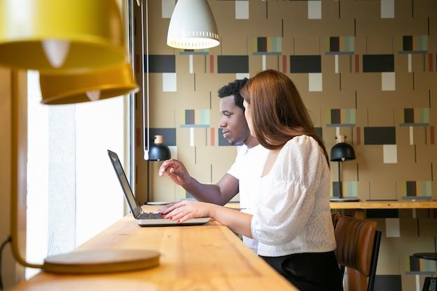 Dos diseñadores multiétnicos sentados juntos y trabajando en una computadora portátil en el espacio de coworking