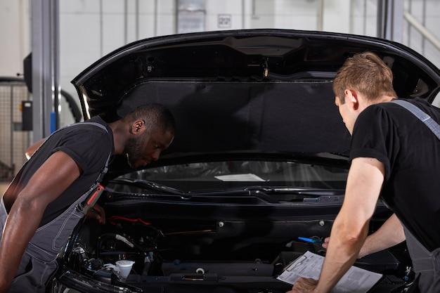 Dos diversos mecánicos de automóviles que cooperan mientras examinan el coche