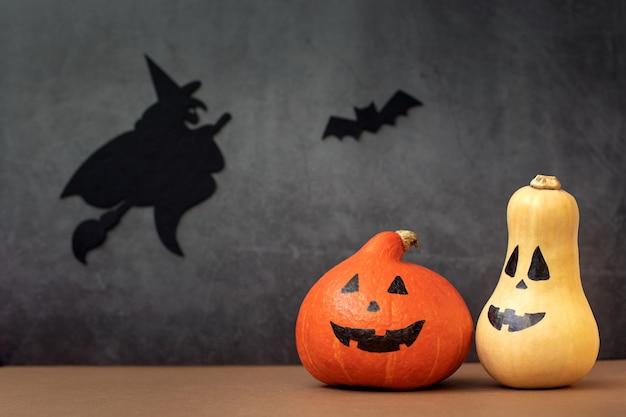 Dos divertidas calabazas de halloween con caras pintadas de brujas y murciélagos sobre un fondo gris oscuro