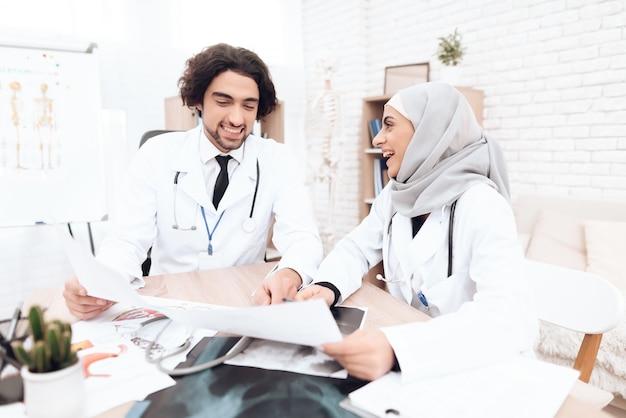 Dos doctores están estudiando los documentos del paciente.