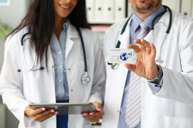 Dos doctores mostrando tarjeta plástica en cámara