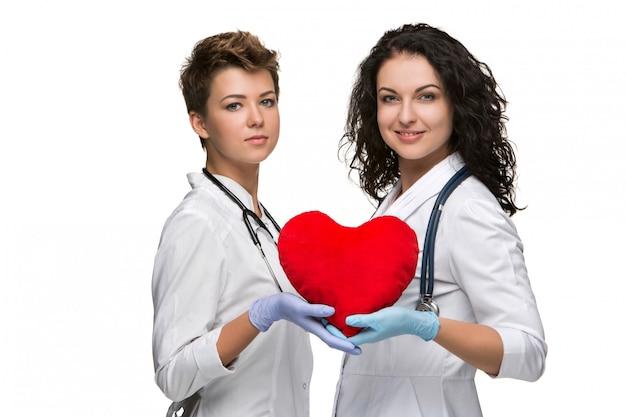 Dos doctores sosteniendo un corazón rojo