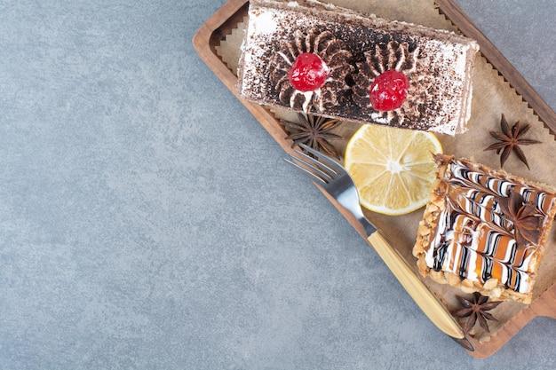 Dos dulces deliciosos trozos de pasteles con anís estrellado sobre tabla de madera