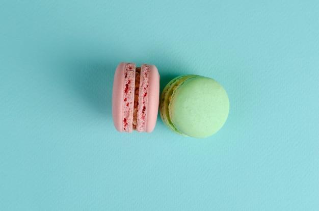 Dos dulces postres franceses de colores pastel verde y rosa macarrones en azul pastel