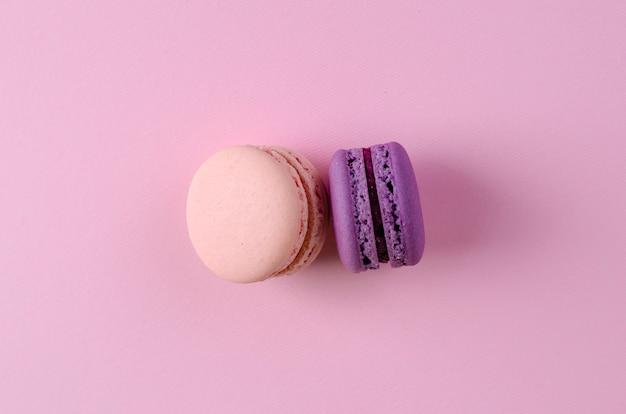 Dos dulces postres franceses de rosa pastel y púrpura macaroonson rosa pastel
