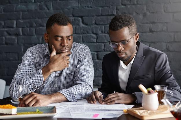 Dos ejecutivos guapos de piel oscura con expresión facial seria y reflexiva