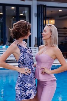 Dos elegante mujer caucásica en vestido de verano y traje rosa de moda
