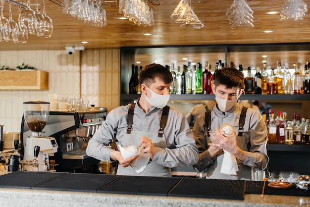 Dos elegantes camareros con máscaras y uniformes durante la pandemia, frotan los vasos para brillar. el trabajo de los restaurantes y cafés durante la pandemia.