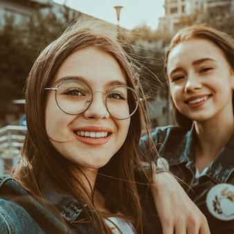Dos elegantes chicas felices mejores amigas haciendo selfie en europa