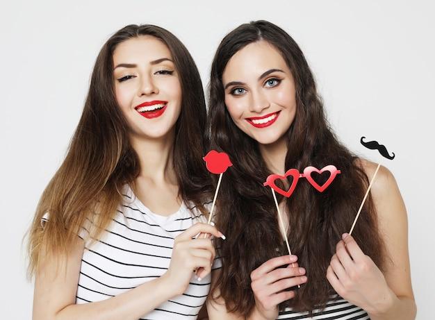 Dos elegantes chicas sexy mejores amigas sosteniendo palos de fiesta de papel