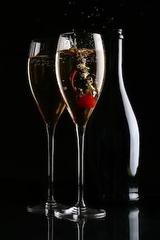Dos elegantes copas con champagne y cereza.