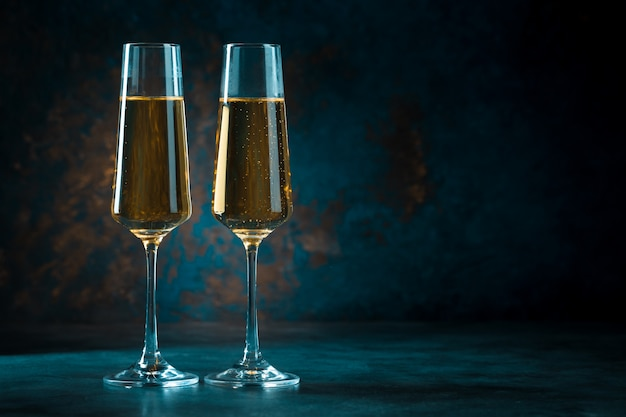 Dos elegantes copas románticas con champán dorado brillante sobre un fondo azul oscuro