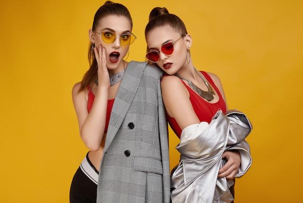 Dos elegantes gemelas hipster glamorosas en top rojo de moda, shorts negros