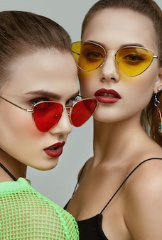 Dos elegantes gemelas hipster glamorosas en vestidos de neón verde de moda