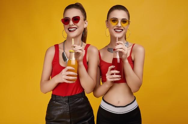 Dos elegantes gemelas hipster glamour en top rojo de moda con bebida cóctel
