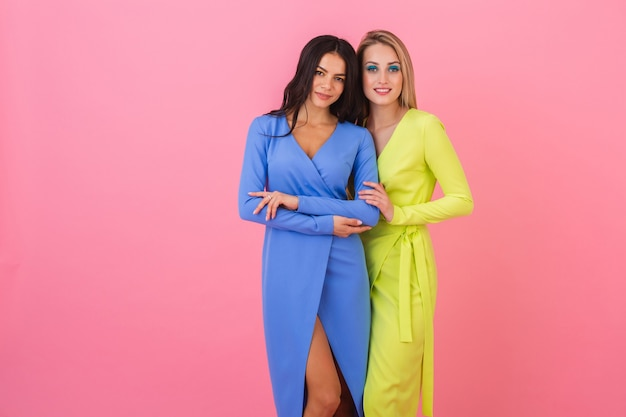 Dos elegantes mujeres atractivas sexy posando en la pared rosada con elegantes vestidos coloridos de color azul y amarillo, tendencia de la moda de verano