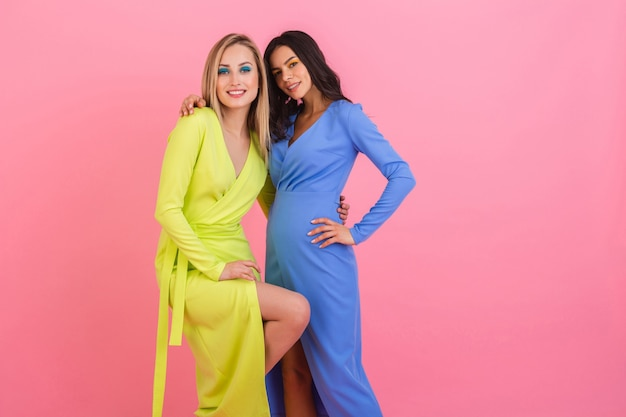 Dos elegantes mujeres atractivas sonrientes sexy posando en la pared rosada en elegantes vestidos coloridos de color azul y amarillo, tendencia de la moda de verano