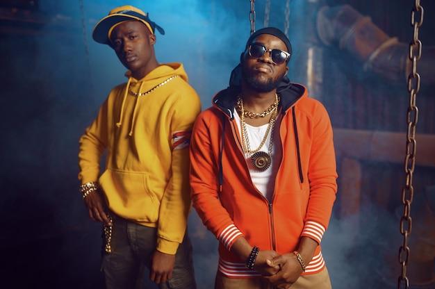Dos elegantes raperos posan con una fresca decoración subterránea. artistas de hip-hop, bailarines de break dance